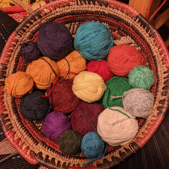 Basket filled with different colored balls of yarn